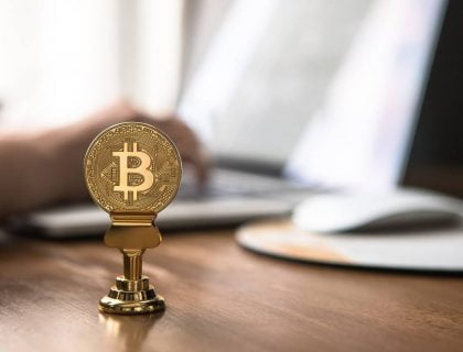 Bitcoin placed in a holder on a desk