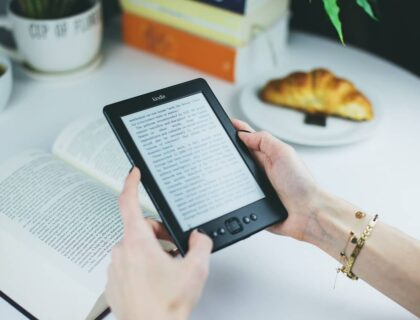 A woman holding an eBook reader in her hands