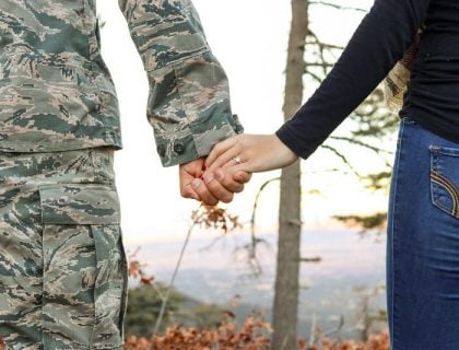 Military man holding his spouse's hand