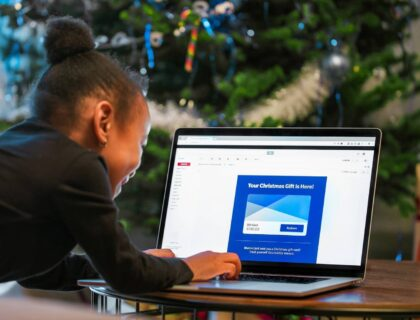 A child opening an email on a laptop