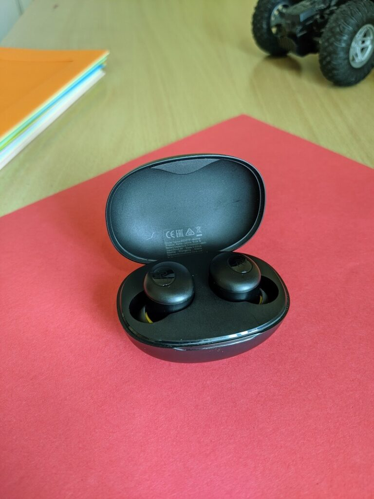 Realme Buds Q placed in its charging case (open)
