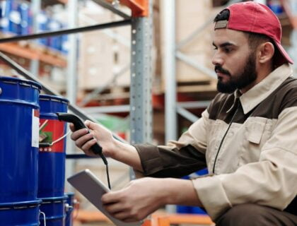 An employee using a tablet and a scanner in the warehouse